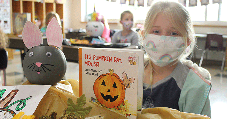 Student with pumpkin based on book character
