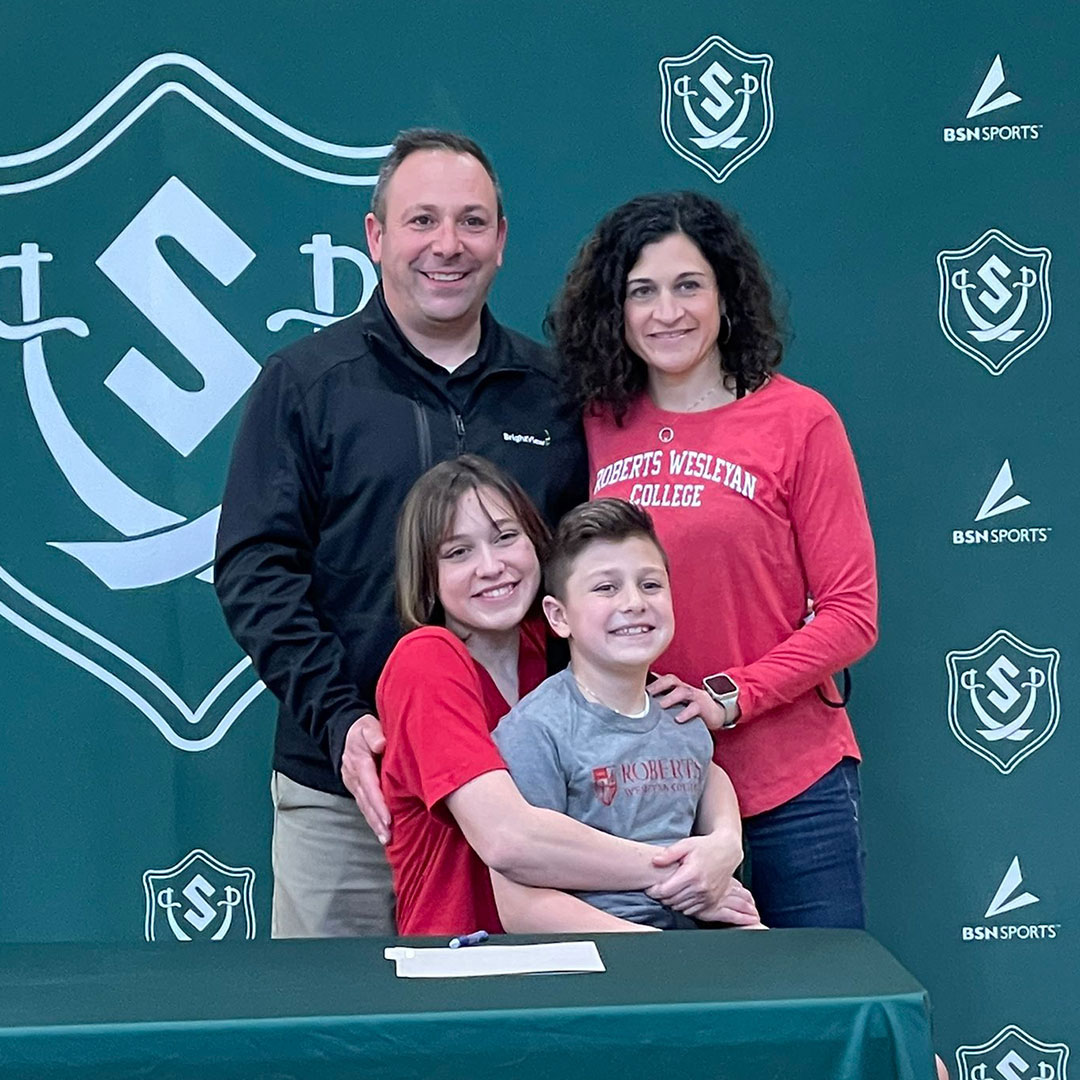 Student surrounded by family for letter of intent signing